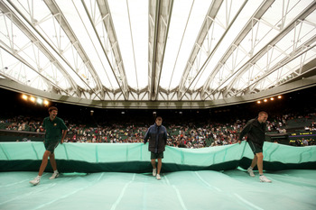 LONDON, ENGLAND - JUNE 28:  The rain tarp is taken off centre court after the roof is closed during rain delay on Day Eight of the Wimbledon Lawn Tennis Championships at the All England Lawn Tennis and Croquet Club on June 28, 2011 in London, England.  (P