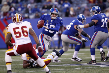Eli Manning tries to illude several Redskins defenders.