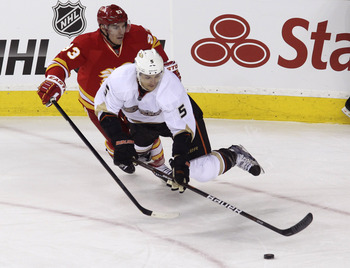 CALGARY, CANADA - APRIL 7: Mike Cammalleri #93 of the Calgary Flames takes a minor penalty for hooking Luca Sbisa #5 of the Anaheim Ducks during second period NHL action on April 7, 2012 at the Scotiabank Saddledome in Calgary, Alberta, Canada. (Photo by