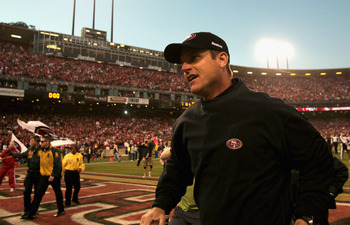 SAN FRANCISCO, CA - JANUARY 14:  Head coach Jim Harbaugh of the San Francisco 49ers celebrates as he runs off the field after winning the NFC Divisional playoff game 36-32 over the New Orleans Saints at Candlestick Park on January 14, 2012 in San Francisc
