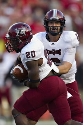 FAYETTEVILLE, AR - SEPTEMBER 17:  Corey Robinson #6 hands off the ball to Shawn Southward #20 of the Troy Trojans during a game against the Arkansas Razorbacks at Donald W. Reynolds Razorback Stadium on September 17, 2011 in Fayetteville, Arkansas.  (Phot