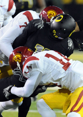 No. 14 Isiah Wiley making a tackle on an Oregon player.