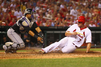 Holliday dodges a tag for a run on July 5 against the Colorado Rockies.