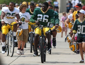 Charlie Peprah rides a child's bike in a training camp tradition.