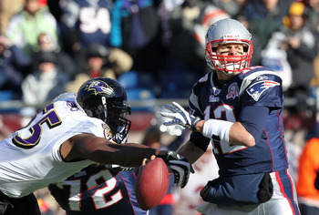 Terrell Suggs tries to strip the ball from Tom Brady.