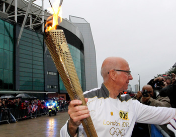 MANCHESTER, ENGLAND - JUNE 24:  Ex Manchester United and England football player Sir Bobby Charlton carries the Olympic Flame on the Torch Relay leg between Salford and Leeds on June 24, 2012 in Manchester, England. The Olympic Flame is now on day 37 of a