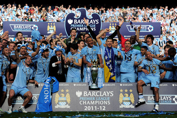 MANCHESTER, ENGLAND - MAY 13:  The Manchester City players celebrate with the trophy following the Barclays Premier League match between Manchester City and Queens Park Rangers at the Etihad Stadium on May 13, 2012 in Manchester, England.  (Photo by Shaun