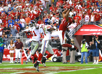 Nov 23, 2008; Glendale, AZ, USA; Arizona Cardinals wide receiver Larry Fitzgerald (11) jumps up to attempt to catch a pass over New York Giants cornerback Aaron Ross (31) and safety Kenny Phillips (21) in the second quarter of a game at University of Phoe