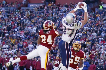 Dec 11, 2011; Landover, MD, USA; New England Patriots tight end Rob Gronkowski (87) catches the ball for a touchdown over Washington Redskins strong safety DeJon Gomes (24) in the first quarter at FedEx Field. Mandatory Credit: Geoff Burke-US PRESSWIRE
