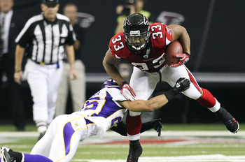November 27, 2011; Atlanta, GA, USA; Atlanta Falcons running back Michael Turner (33) shakes a tackle by Minnesota Vikings linebacker Kenny Onatolu (55) in the first quarter of the game at the Georgia Dome. Mandatory Credit: Daniel Shirey-US PRESSWIRE