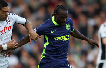 LONDON, ENGLAND - APRIL 21:  Clint Dempsey of Fulham and Victor Moses of Wigan Athletic tussle for the ball during the Barclays Premier League match between Fulham and Wigan Athletic at Craven Cottage on April 21, 2012 in London, England.  (Photo by Julia