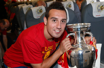 IN FLIGHT - JULY 02:  In this handout image supplied by the Royal Spanish Football Federation, Santi Cazorla of Spain poses with the trophy following his team's victory in the UEFA EURO 2012 final match against Italy onboard the Spain team's airplane duri