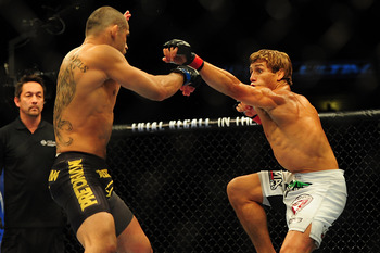 Jul 21, 2012; Calgary, AB, CANADA; Renan Barao (blue golves) and Urijah Faber (red gloves) during the interim bantamweight title bout of UFC 149 at the Scotiabank Saddledome. Mandatory Credit: Anne-Marie Sorvin-US PRESSWIRE