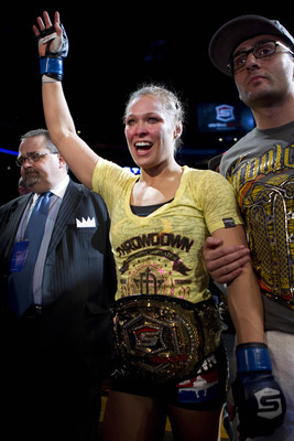 March 3, 2012; Columbus, OH, USA; New champion Ronda Rousey  is escorted out of the arena by trainer Edmond Tarverdyan after defeating Miesha Tate during the Strikeforce Grand Prix final at Nationwide Arena. Mandatory Credit: Greg Bartram-US PRESSWIRE