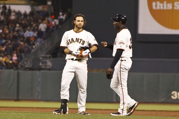SAN FRANCISCO, CA - JULY 23: Brandon Crawford #35 of the San Francisco Giants (left) reacts next to first base coach Roberto Kelly #39 after getting ejected from the game by first base umpire Jordan Baker #71 (not pictured) during the eighth inning agains