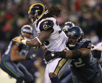 Brandon Mebane, right, rips down St. Louis running back Steven Jackson.