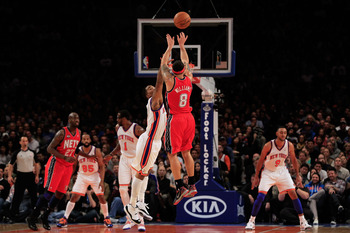NEW YORK, NY - FEBRUARY 20:  Deron Williams #8 of the New Jersey Nets shoots a three pointer over J.R. Reid of the New York Knicks at Madison Square Garden on February 20, 2012 in New York City. NOTE TO USER: User expressly acknowledges and agrees that, b