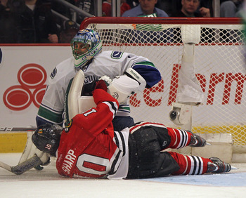 CHICAGO, IL - MARCH 21: Patrick Sharp #10 of the Chicago Blackhawks collides with Roberto Luongo #1 of the Vancouver Canucks at the United Center on March 21, 2012 in Chicago, Illinois. The Blackhawks defeated the Canucks 2-1 in overtime.(Photo by Jonatha
