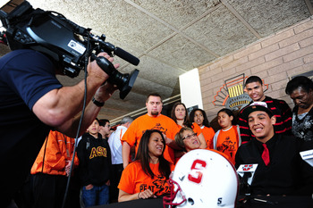 Feb. 1, 2012; Tempe AZ, USA; Corona del Sol Aztecs offensive lineman Andrus Peat (bottom right) is surrounded by friends and family at a press conference at Corona del Sol High School to announce his decision to play college football for the Stanford Card