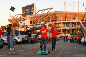 MIAMI GARDENS, FL - JANUARY 04:  Fans of the Clemson Tigers play a bean bag toss game in the parking lot as they tailgate prior to Clemson playing against the West Virginia Mountaineers during the Discover Orange Bowl at Sun Life Stadium on January 4, 201