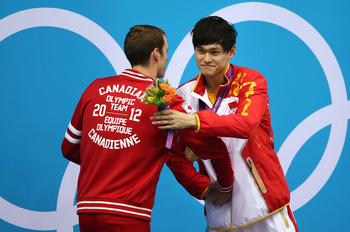 LONDON, ENGLAND - AUGUST 04:  Silver medallist Ryan Cochrane of Canada congratulates gold medallist Yang Sun of China on the podium during the medal ceremony for the Men's 1500m Freestyle Final on Day 8 of the London 2012 Olympic Games at the Aquatics Cen