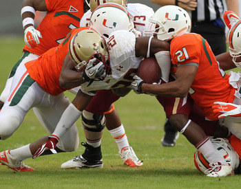 NOV 25, 2011; Miami Gardens, FL, USA; Boston College Eagles running back Tahj Kimble (20) is tackled by Miami Hurricanes linebacker Denzel Perryman (52) and Miami Hurricanes defensive back Brandon McGee (21) at Sun Life Stadium. Mandatory Credit: Robert M