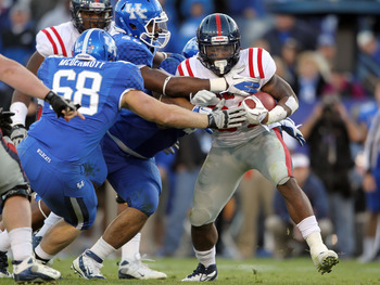 LEXINGTON, KY - NOVEMBER 05:  Brandon Bolden #34 of the Mississippi Rebels is tackled by Luke McDermott #68, Avery Williamson #40 and Ridge Wilson #48 of the Kentucky Wildcats at Commonwealth Stadium on November 5, 2011 in Lexington, Kentucky.  (Photo by