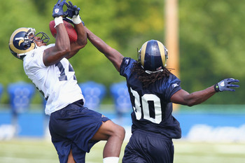 Jalil Carter (14) and Dionte Dinkins (30) compete for control of a pass during training camp at the Russell Training Center on July 31, 2011 in Earth City, Missouri. Many positions are still up for grabs, too.