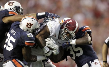Nov 26, 2011; Auburn, AL, USA; Auburn Tigers linebackers Daren Bates (25) and Jonathan Evans (35) tackle Alabama Crimson Tide running back Mark Ingram (3) during the second half at Jordan-Hare Stadium.  The Crimson Tide beat the Tigers 42-14.  Mandatory C