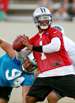 Cam Newton (1) throws a pass on the first day of training camp.