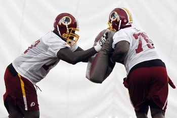May 21, 2012; Ashburn, VA, USA; Washington Redskins tackle Jammal Brown (77) and Redskins tackle James Lee (75) participate in a blocking drill during organized team activities at Redskins Park. Mandatory Credit: Geoff Burke-US PRESSWIRE