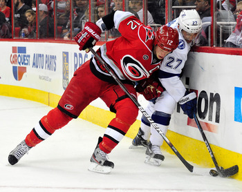 RALEIGH, NC - MARCH 03:  Bruno Gervais #27 of the Tampa Bay Lightning battles for the puck with Eric Staal #12 of the Carolina Hurricanes during play at the RBC Center on March 3, 2012 in Raleigh, North Carolina.  (Photo by Grant Halverson/Getty Images)