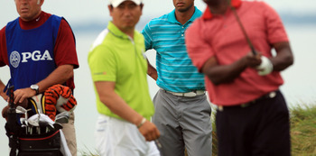 Tiger Woods looks on intently as Vijay Singh hits a shot