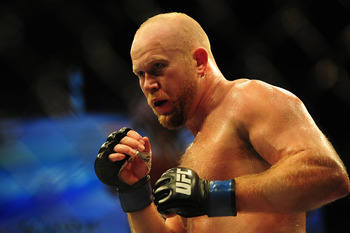 Jul 21, 2012; Calgary, AB, CANADA; Tim Boetsch (blue gloves) during the middleweight bout of UFC 149 against  and Hector Lombard (not pictured) at the Scotiabank Saddledome. Mandatory Credit: Anne-Marie Sorvin-US PRESSWIRE