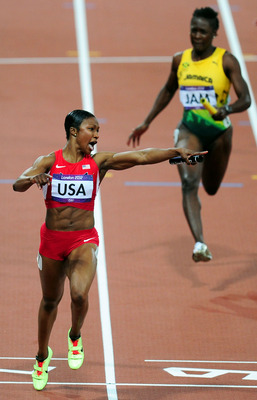 Jeter of the United States pointing at the time clock as she crosses the finish line.