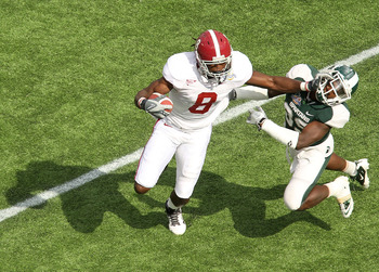 ORLANDO, FL - JANUARY 01: Julio Jones #8 of the Alabama Crimson Tide stiffarms Chris Rucker #29 of  the Michigan State Spartans during the Capitol One Bowl at the Florida Citrus Bowl on January 1, 2011 in Orlando, Florida.  (Photo by Mike Ehrmann/Getty Im