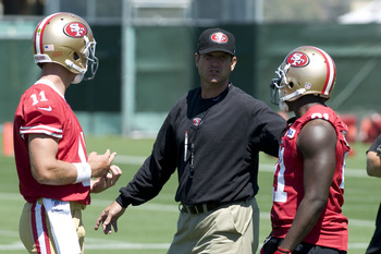 July 27, 2012; Santa Clara, CA, USA; San Francisco 49ers head coach Jim Harbaugh talks with quarterback Alex Smith (11) and running back Frank Gore (21) during training camp at the 49ers practice facility.  Mandatory Credit: Ed Szczepanski-US PRESSWIRE