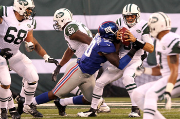 August 18, 2012; East Rutherford, NJ, USA; New York Jets quarterback Mark Sanchez (6) is sacked by New York Giants defensive end Jason Pierre-Paul (90) during the first quarter of a preseason game at MetLife Stadium. Mandatory Credit: Brad Penner-US PRESS