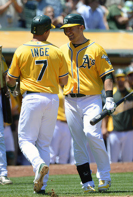Cliff Pennington (right) high fives Brandon Inge who returns to the dugout after scoring.