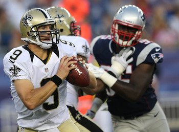 FOXBORO, MA - AUGUST 9:    Drew Brees #9 of the New Orleans Saints is chased by  Chandler Jones #95 of the New England Patriots in the first half at Gillette Stadium on August 9, 2012 in Foxboro, Massachusetts. (Photo by Jim Rogash/Getty Images)