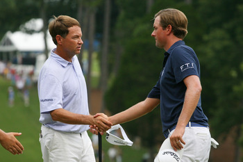 Webb Simpson shakes hands with his Ryder Cup captain, Davis Love III (left)