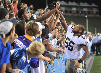 Aug 5, 2012; Canton, OH, USA; New Orleans Saints linebacker Ezra Butler (55) hands his gloves to a fan after the pro football hall of fame preseason game against the Arizona Cardinals at Fawcett Stadium. Mandatory Credit: David Richard-US PRESSWIRE