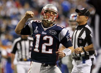 Feb 5, 2012; Indianapolis, IN, USA; New England Patriots quarterback Tom Brady (12) celebrates after throwing a touchdown pass during Super Bowl XLVI against the New York Giants at Lucas Oil Stadium.  Mandatory Credit: Chris Faytok/THE STAR-LEDGER via US