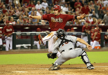 PHOENIX, AZ - AUGUST 22:  Aaron Hill #2 of the Arizona Diamondbacks is tagged out at home plate by catcher Rob Brantly #19 of the Miami Marlins as he attempts to score a run in the ninth inning of game two of the MLB double header at Chase Field on August