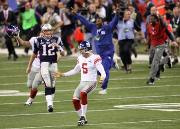 INDIANAPOLIS, IN - FEBRUARY 05:  Steve Weatherford #5 and Henry Hynoski #45 of the New York Giants celebrates as Tom Brady #12 of the New England Patriots looks on after Super Bowl XLVI at Lucas Oil Stadium on February 5, 2012 in Indianapolis, Indiana.  (