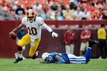 LANDOVER, MD - AUGUST 25:  Robert Griffin III #10 of the Washington Redskins avoids a tackle by Kavell Conner #53 of the Indianapolis Colts during a preseason game at FedExField on August 25, 2012 in Landover, Maryland.  (Photo by Patrick McDermott/Getty
