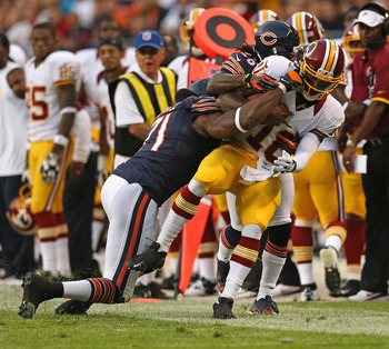 CHICAGO, IL - AUGUST 18: Robert Griffin III #10 of the Washington Redskins is knocked out of bounds by Israel Idonije #71 and Tim Jennings #26 of the Chicago Bears during a preseason game at Soldier Field on August 18, 2012 in Chicago, Illinois.  (Photo b
