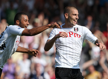LONDON, ENGLAND - AUGUST 18:   Mladen Petric of Fulham (R) celebrates his second goal with team mate Moussa Dembele during the Barclays Premier League match between Fulham and Norwich City at Craven Cottage on August 18, 2012 in London, England.  (Photo b