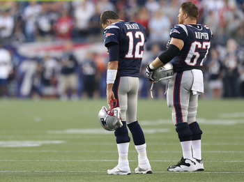 FOXBORO, MA - AUGUST 9:   Tom Brady #12 and Dan Koppen #67 of the New England Patriots participate in a moment of silence for Junior Seau before a preseason game against the Orleans Saints in the first half at Gillette Stadium on August 9, 2012 in Foxboro