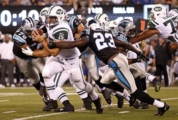 EAST RUTHERFORD, NJ - AUGUST 26:  Tim Tebow #15 of the New York Jets tries to break free of Sherrod Martin #23 of the Carolina Panthers during their preseason game at MetLife Stadium on August 26, 2012 in East Rutherford, New Jersey.  (Photo by Jeff Zelev